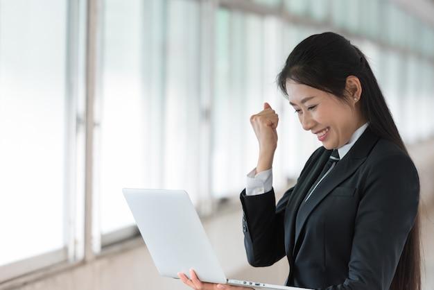 ノートパソコンを見て素晴らしい仕事のジェスチャーを持つ女性実業家。 Premium写真