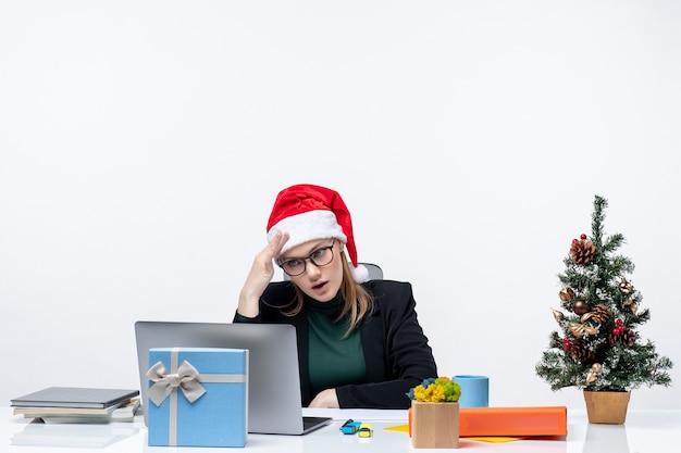 Donna d'affari con il suo cappello di babbo natale seduto a un tavolo con un albero di natale e un regalo Foto Gratuite