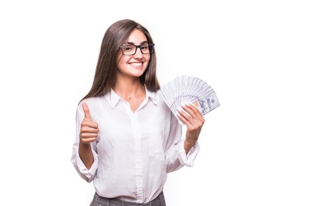 Деловая женщина с длинными каштановыми волосами в повседневной одежде держит много долларовых банкнот над белой Бесплатные Фотографии