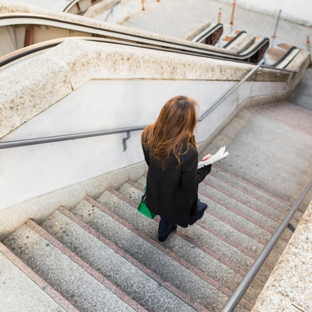 Business woman with newspaper walking down stairs Free Photo