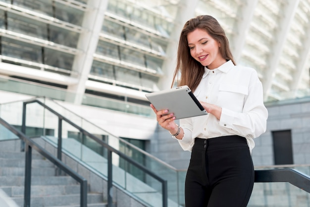 Business woman with a tablet in the street Free Photo