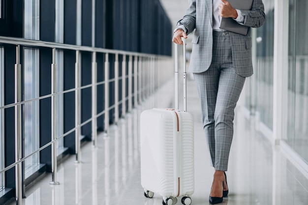 Business woman with travel luggage in airport, holding laptop Free Photo