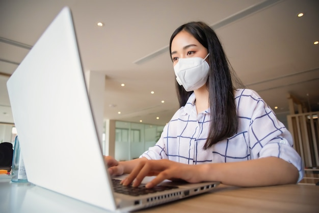 Business woman working from home wearing protective mask and using laptop computer. coronavirus outbreak Premium Photo