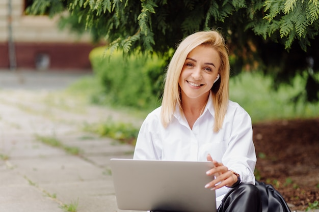 Business woman working on laptop computer outside in city park Free Photo