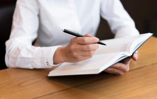 Business woman writing in agenda Free Photo