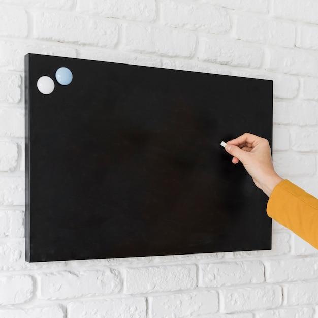 Business woman writing on chalkboard Free Photo