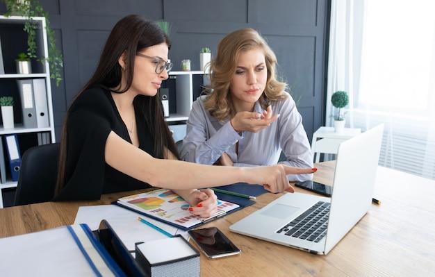ノートパソコン、チームワークの概念に一緒に取り組んでいるオフィスの机でビジネス女性 Premium写真