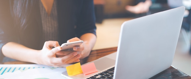 Business women hand are uses a smartphone and use a laptop computer in office. Premium Photo