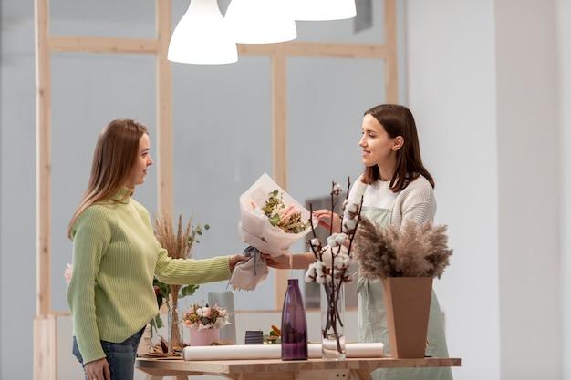 Бизнес женщины, работающие в цветочном магазине, сидя боком Бесплатные Фотографии