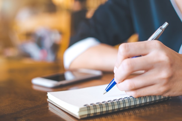 Business women writing on a notebook Premium Photo