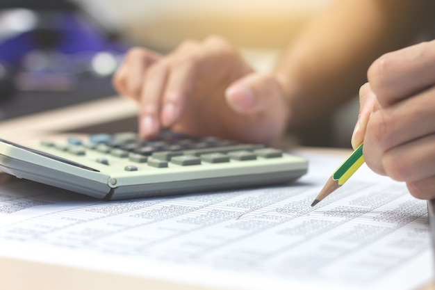 Businessman accountant hand holding pencil working on calculator to calculate financial Premium Photo