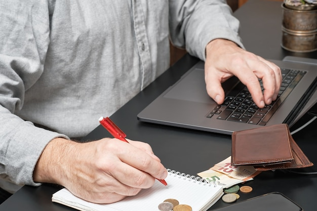 Businessman or accountant holding pen working at desk using a laptop to calculate financial report Free Photo
