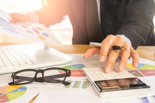 Businessman or accountant working on calculator to calculate business data concept at office. Premium Photo