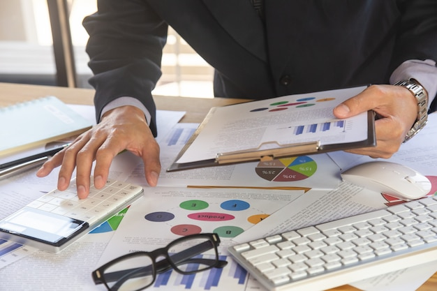 Businessman or accountant working on calculator to calculate business data concept. Premium Photo