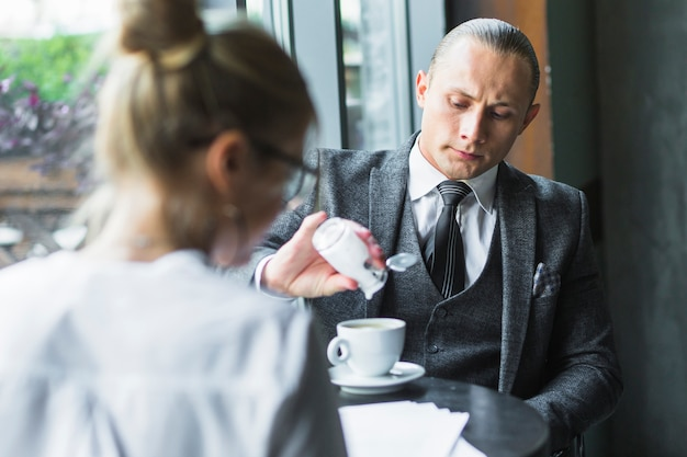 Businessman adding sugar in coffee Free Photo