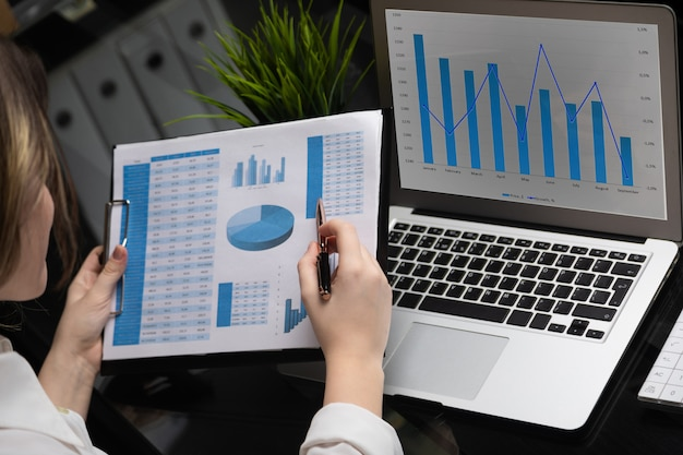 Businessman analyzing investment charts with laptop. accounting Premium Photo