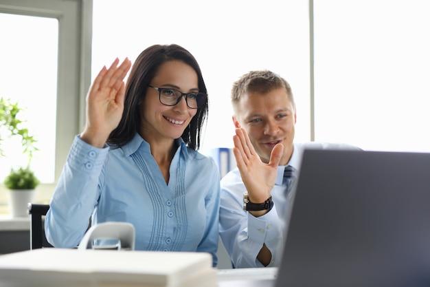 ビジネスマンやオフィスのビジネスウーマンがビデオコミュニケーションを介して対話者に挨拶します。 Premium写真