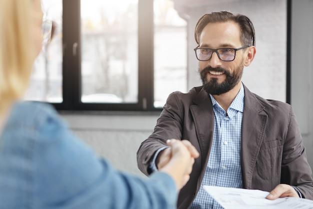 Бизнесмен и бизнесвумен пожимают друг другу руки после успешного подписания контракта Бесплатные Фотографии
