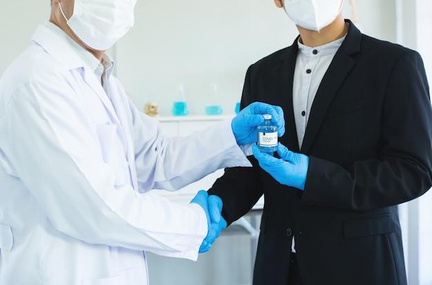 ビジネスマンと医師が手を振って合意covid19ワクチンを手に。 Premium写真