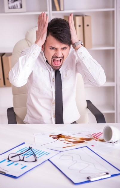 Businessman angry over spilled coffee on documents. Premium Photo