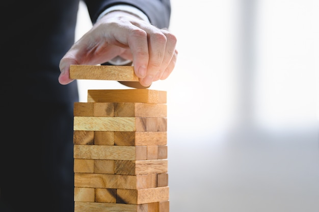 Businessman arranging wood block and stacking as tower by hand. Premium Photo