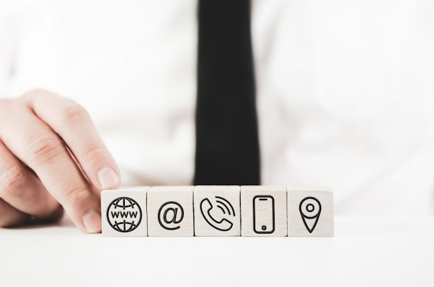 Businessman assembling white blocks with contact icons printed on them Premium Photo