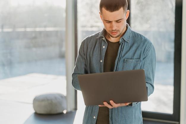 ノートパソコンを持つオフィスでビジネスマン 無料写真