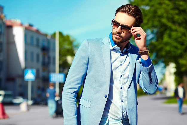 Businessman in blue suit wearing sunglasses in the street Free Photo