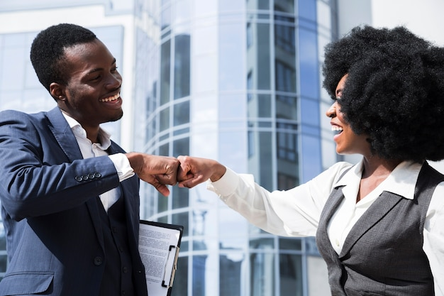 Businessman and businesswoman bumping their fist in front of corporate building Free Photo