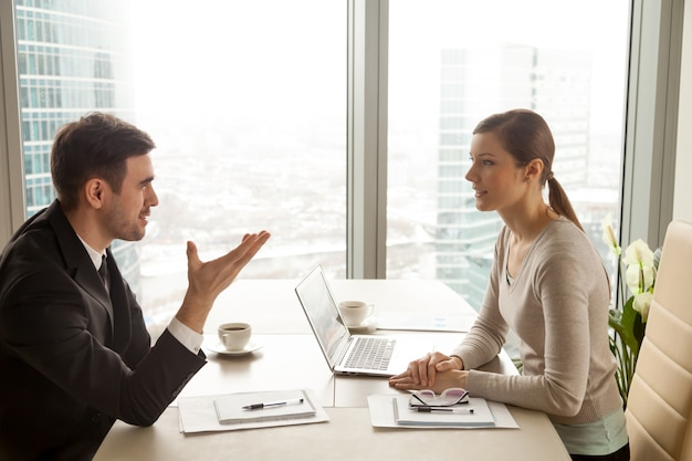 Businessman and businesswoman discussing work at office desk Free Photo