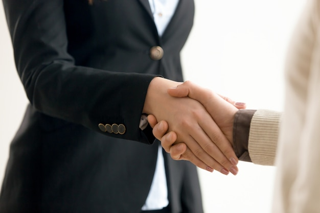 Businessman and businesswoman shaking hands, business handshake close up view Free Photo