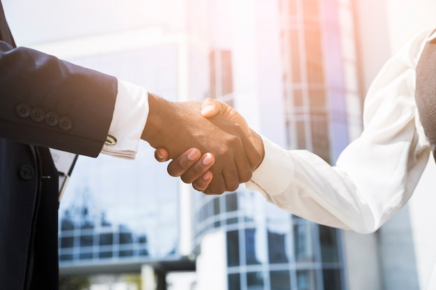 Businessman and businesswoman shaking hands in front of corporate building Free Photo