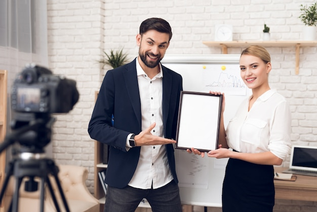 Businessman and businesswoman showing blank diploma. Premium Photo