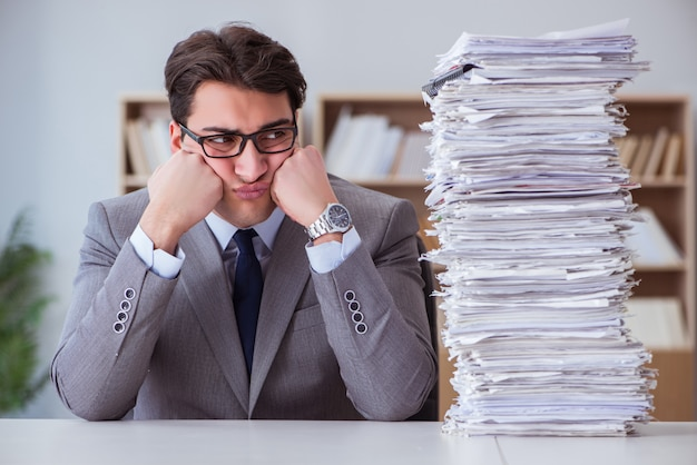 Businessman busy with paperwork in office | Botkeeper