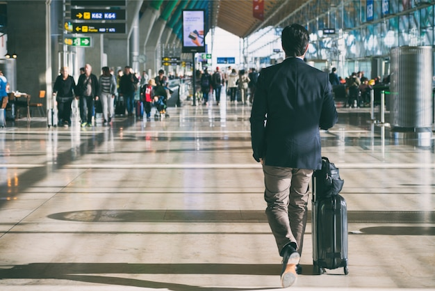 Businessman carrying suitcase while walking through a passenger departure terminal Premium Photo