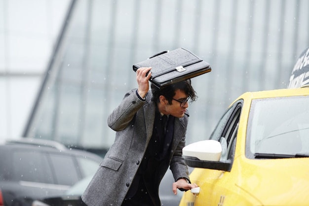 Businessman catching taxi in storm Free Photo