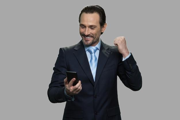 스마트 폰에서 메시지를 읽는 동안 성공을 축 하하는 사업가. 사업 성공과 성취. 프리미엄 사진