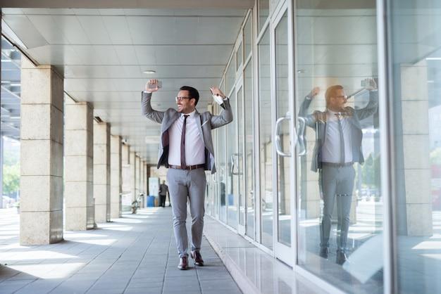 직장에서 성공을 축 하하는 사업가. 한 손으로 태블릿과 다른 스마트 폰에서. 프리미엄 사진