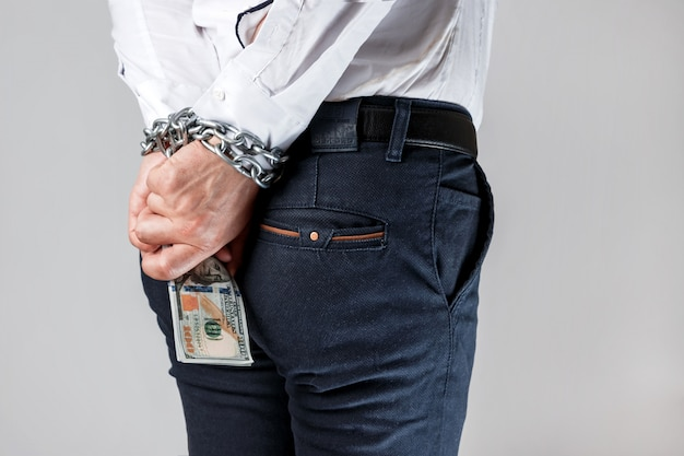 Businessman in chains with dollars Premium Photo