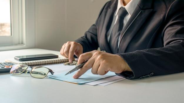 当座預金口座と事業収入、財務管理の概念、および資金調達のビジネスマン。 Premium写真