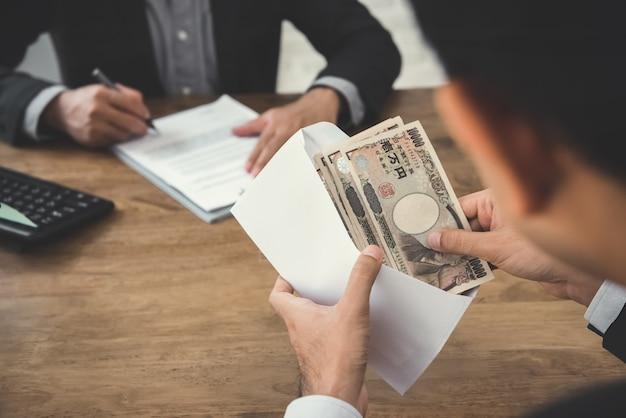 Businessman checking japanese yen money in the envelope Premium Photo