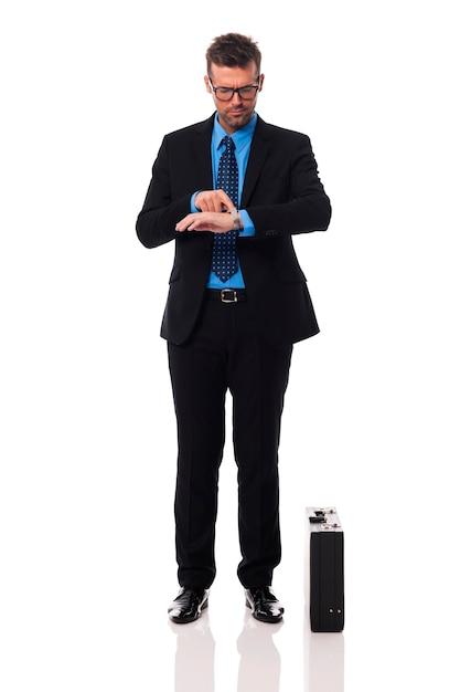 ビジネスマンが時計で時間をチェック 無料写真