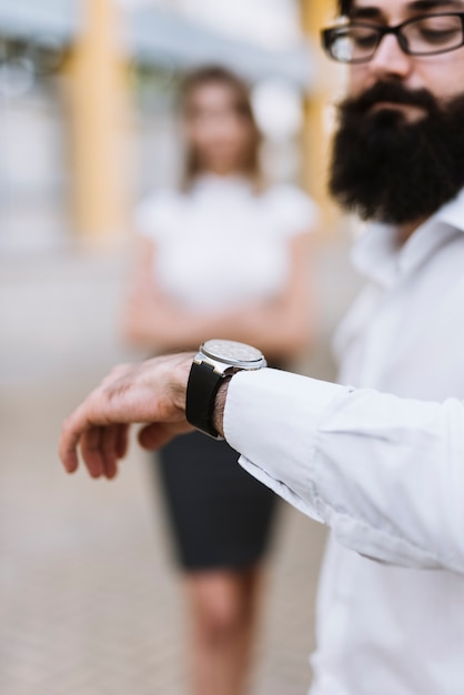 A businessman checking time on wrist watch with blurred female colleague in the background Free Photo