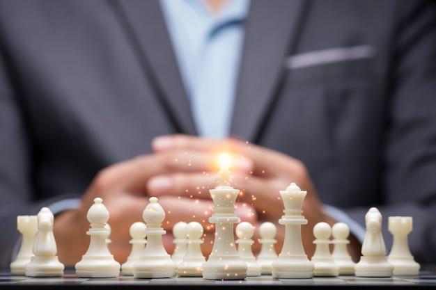 ビジネスマンは滑走戦略を考えるための群衆チェスの数字の後ろに手を握りしめた。競争のある事業計画と戦略的事業戦術。 Premium写真