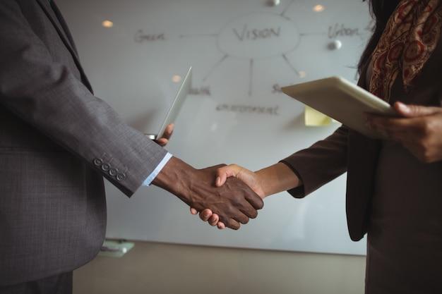 Uomo d'affari e un collega si stringono la mano Foto Gratuite
