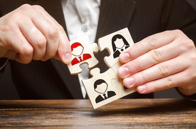 A businessman collects puzzles, team of employees Premium Photo