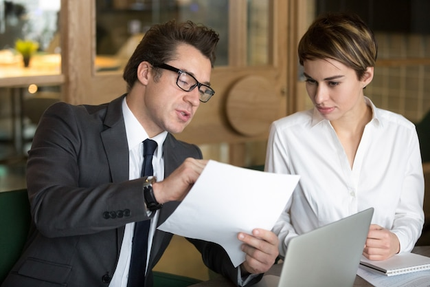 Businessman consulting with female colleague on contract conditions Free Photo