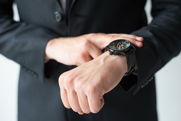 Businessman consulting wristwatch Free Photo