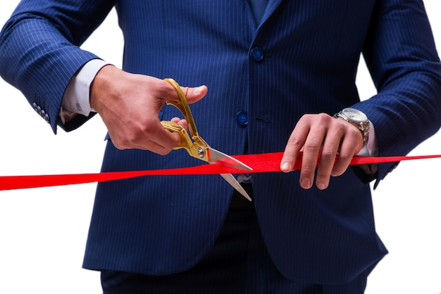 Businessman cutting red ribbon isolated on white Premium Photo