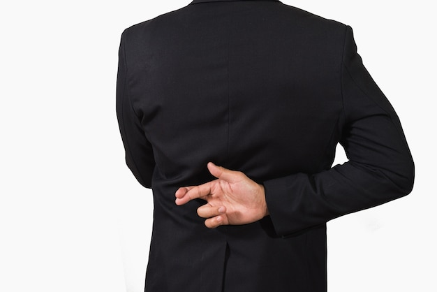 Businessman in dark suit with crossed fingers behind his back Premium Photo